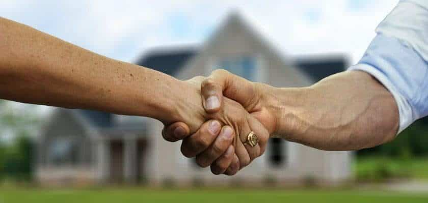 residential movers Arlington - people shaking hands in front of the house